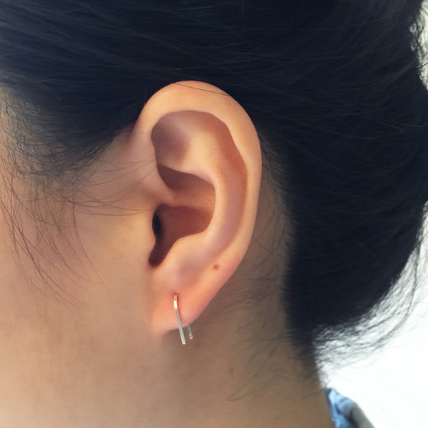 Model wearing Short U-shape wire Earrings with single post in - rose gold