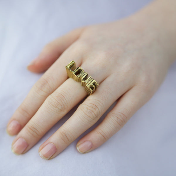 Hand wearing brass 3d love ring