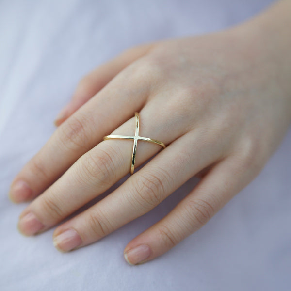 Hand wearing yellow gold X ring