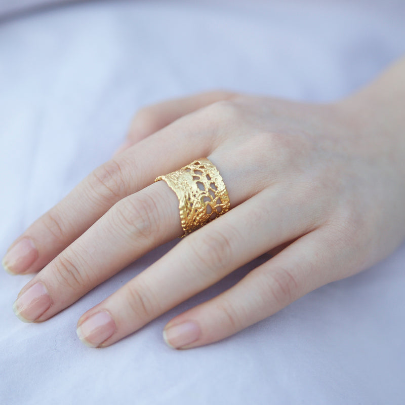 Hand wearing yellow gold lace ring with other rings