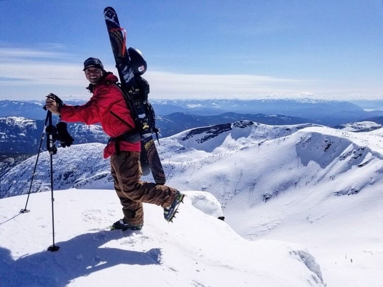 person standing on snowy mountain peak with skis and crampons