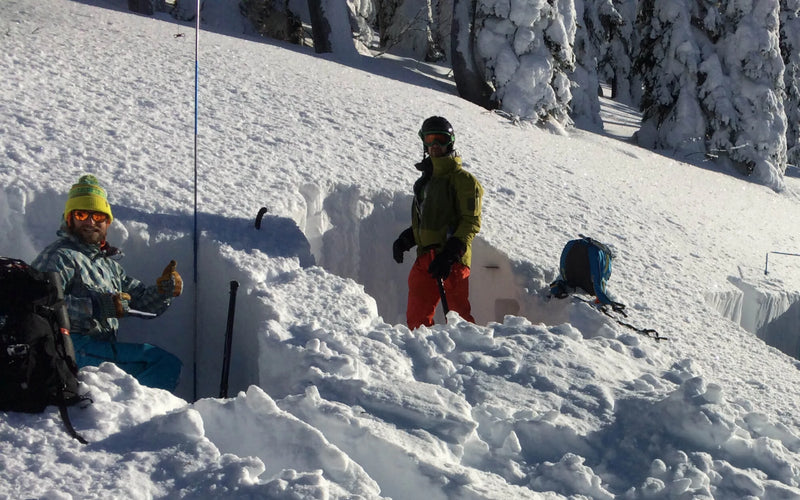 backcountry skiers digging snow pits