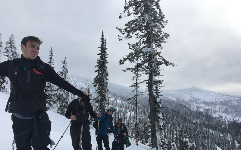 backcountry skiers pause while skinning