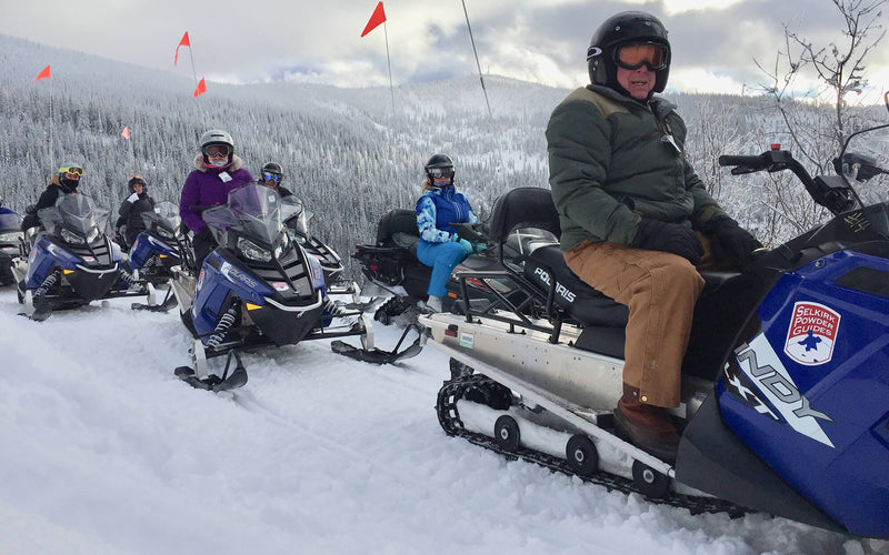 snowmobile group parked in mountain valley