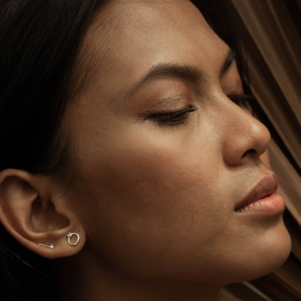 A woman wearing jumna studs and tage studs on the right ear