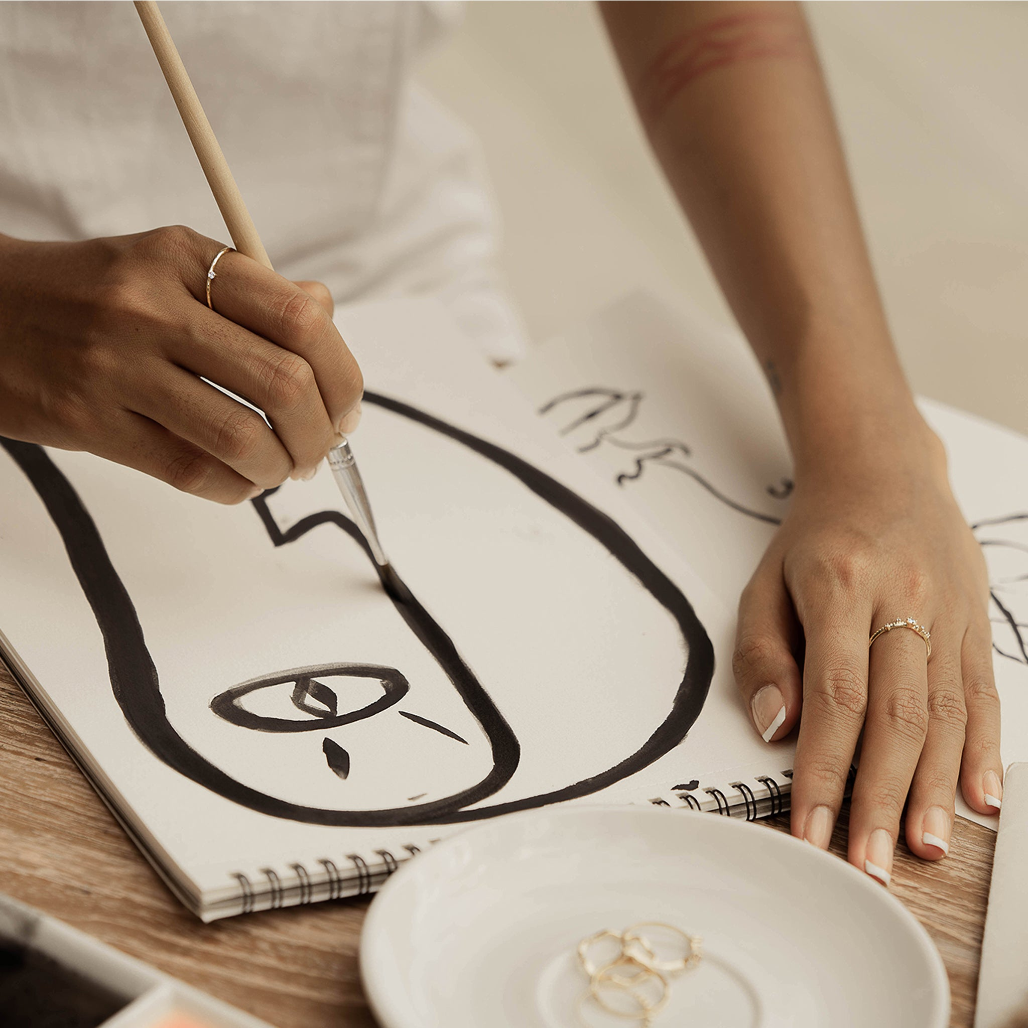 A woman painting a face and wearing Ili ring and Kasai ring from Sceona fine jewellery