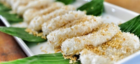 A close up photo of a set of Palitaw laid on top of banana leaves and white plate.