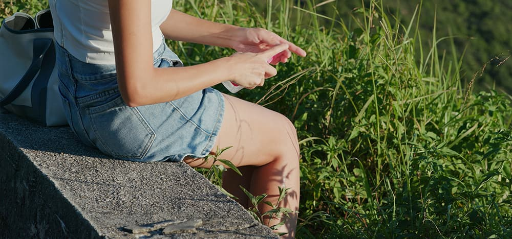 Woman applying topical insect repellent