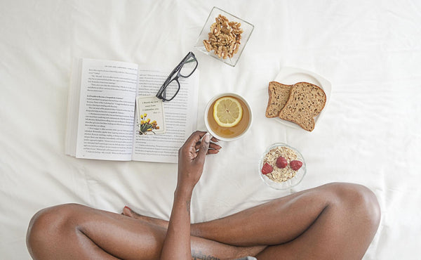 Woman sitting cross legged on bed with lemon tea, toast, oatmeal, fruit, and book.