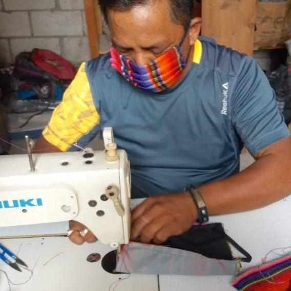 artisan making multicolor sarape facemask in guatemala