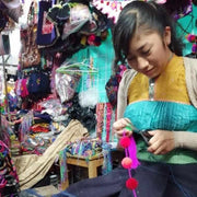 mexican artisan woman from chiapas making pompoms lumily