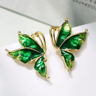 Vibrantly colourful enamel earrings with a butterfly motif, available in blue, green, purple, and red.