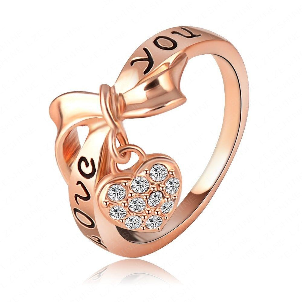 Be Still My Heart Ring - A rose gold ring with a heart and ribbon theme.