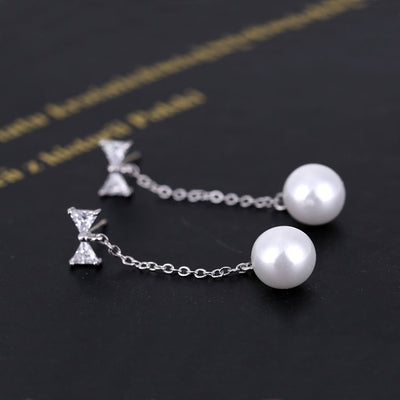 Adorable long dangling stud earrings with a crystal bow and a pearl at the end.