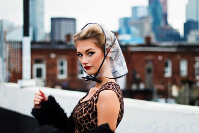 A young woman dressed in rockabilly fashion wearing a cute rain bonnet from The Bonnit.