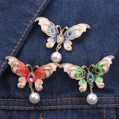 A lovely butterfly brooch with rhinestone crystal and pearls available in blue, green, and pink.