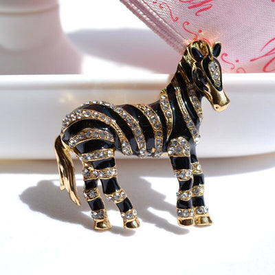 Zealous Zebra Brooch - A medium sized brooch shaped like a zebra standing still and looking forward, with a gold and black enamel background and studded with small crystals.