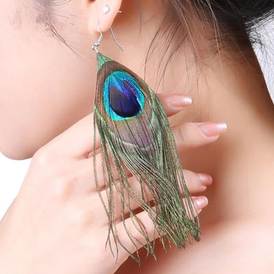 A woman wearing large, elegant peacock feather earrings.