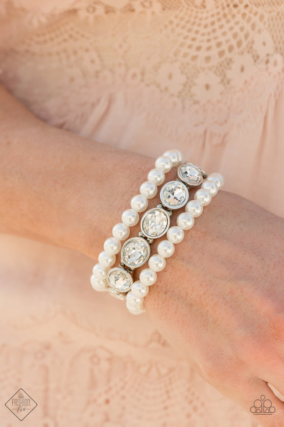 Flawlessly Flattering - White Pearl Bracelet - Paparazzi Accessories   A strand of oversized oval white gems is paired with two stretchy pearl beaded bracelets, stacking up the wrist in a glamorous finish. Each strand is threaded along stretchy bands, creating a versatile fit. Sold as one set of three bracelets.