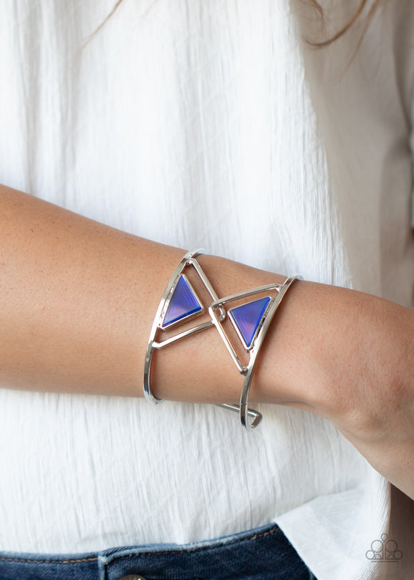 Pyramid Palace - Blue Iridescent & Silver - Cuff Bracelet - Paparazzi Accessories  Featuring an iridescent finish, a pair of blue acrylic triangles dot the centers of two overlapping silver triangle frames inside an airy silver cuff for an edgy fashion. Sold as one individual bracelet.