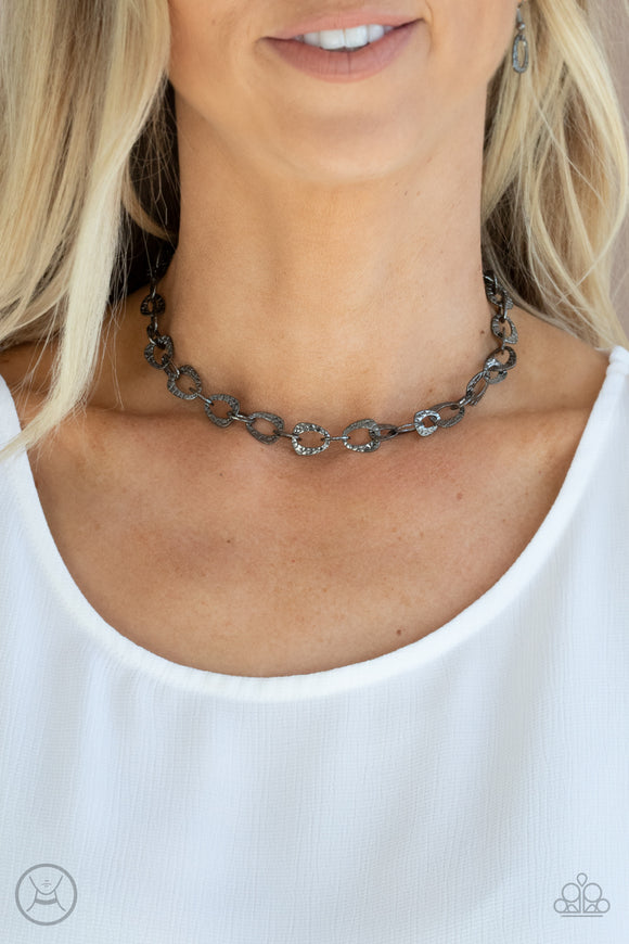 Urban Safari - Black - Gunmetal Choker Necklace and Earrings - Paparazzi Accessories  Embossed in a metallic crocodile-like print, asymmetrical gunmetal links delicately connect around the neck for a wild industrial inspired look. Features an adjustable clasp closure. Sold as one individual choker necklace. Includes one pair of matching earrings.