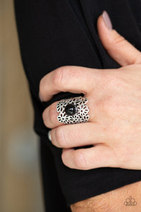 Flower Shower - Black Ring - Paparazzi Accessories   A collection of airy silver flowers coalesce into a thick silver band. A polished black bead dots the center, adding a perfect pop of color to the seasonal piece. Features a stretchy band for a flexible fit. Sold as one individual ring. Paparazzi Accessories are Lead and Nickel Free.