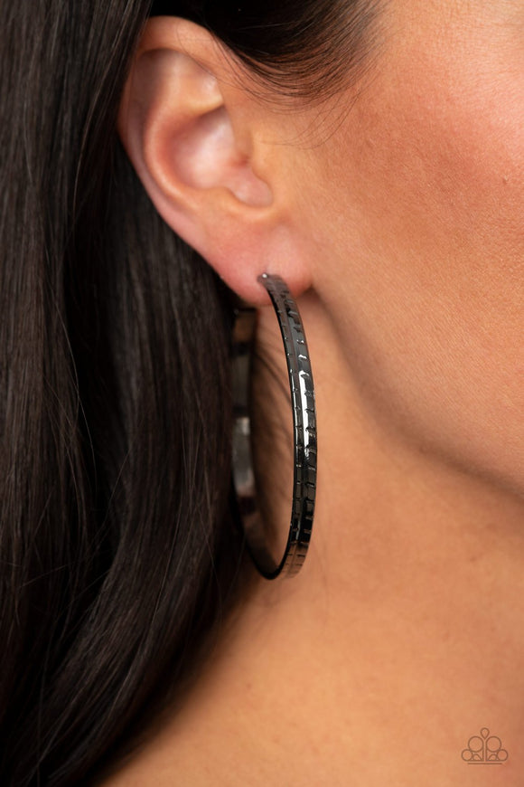 TREAD All About It - Black - Gunmetal Hoop Earrings - Paparazzi Accessories  Etched and embossed in a tread-like pattern, an oversized gunmetal hoop curls around the ear for an edgy look. Earring attaches to a standard post fitting. Hoop measures approximately 2 1/4