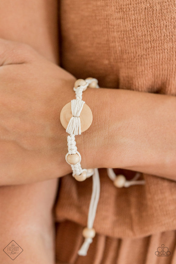 The Road KNOT Taken White Bracelet - Paparazzi Accessories  Infused with a wooden button-like centerpiece, pieces of earthy white cording delicately knot wooden beads in place around the wrist for a homespun braided look. Features an adjustable sliding knot closure. Sold as one individual bracelet.