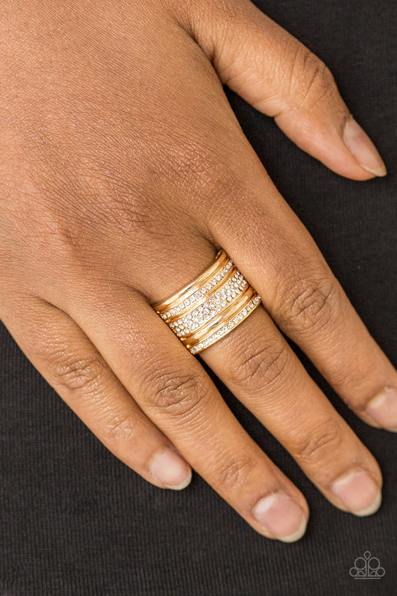 Top Dollar Drama - Gold Ring - Flexible Fit - Paparazzi Accessories  Shimmery gold and white rhinestone encrusted bands stack across the finger for a glamorous look. Features a stretchy band for a flexible fit. Sold as one individual ring.