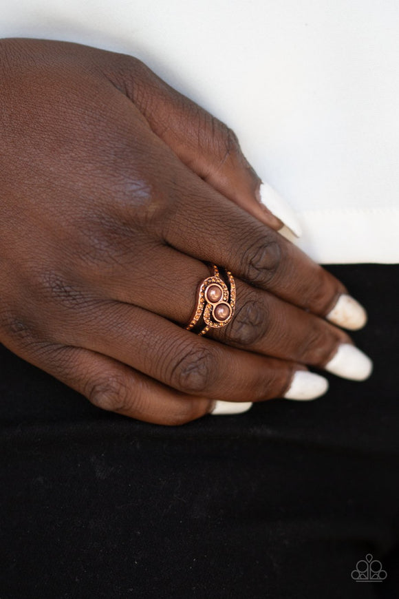 Collect Up Front - Copper Ring - Paparazzi Accessories  Glittery topaz rhinestone encrusted bands swirl around a pair of coppery pearls for a refined look. Features a dainty stretchy band for a flexible fit. Sold as one individual ring. Paparazzi Accessories are Lead & Nickel Free.