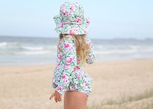 Girls swimsuit and sun hat in Pink Bloom at the beach