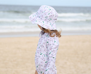 Sun hat and girls swimsuit in Floral Whisper at the beach