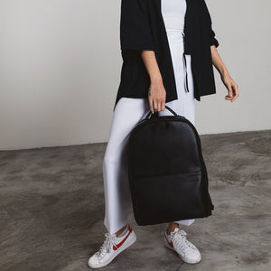 Monochrome outfit with black vegan leather camera backpack