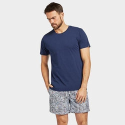 Man wearing Academy Brand Basic Crew cotton T-shirt in Riviera Blue colour with boardshorts, hand in pocket, front view