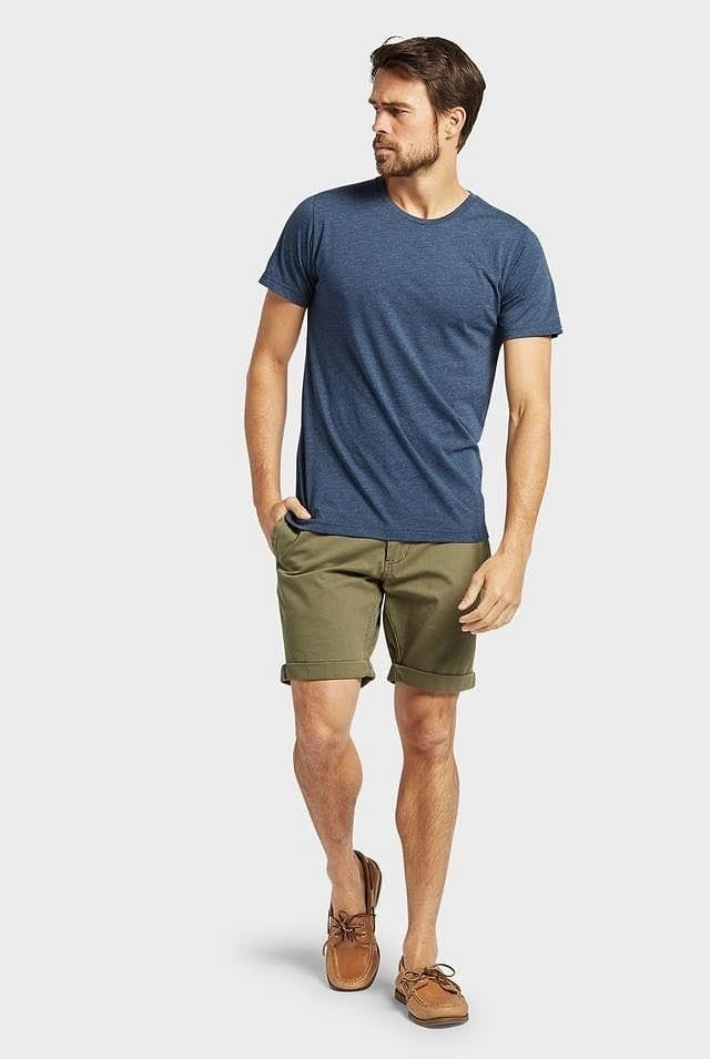 Full body view of man wearing Academy Brand Basic Crew cotton t-shirt in navy marle colour, olive coloured shorts & tan leather shoes.