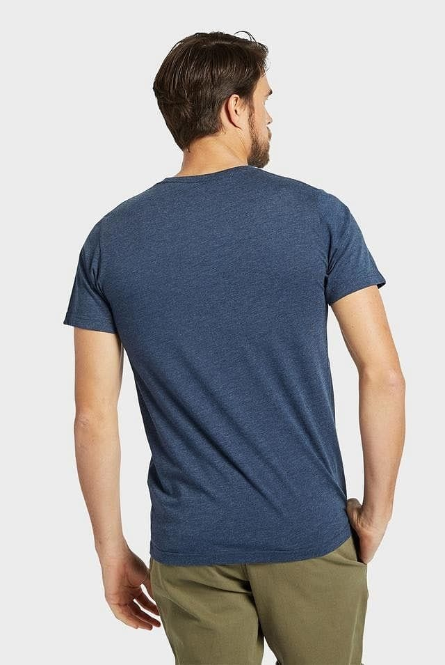 Man wearing Academy Brand Basic Crew cotton t-shirt in navy marle colour, standing casually with his right hand in pocket.  Back view.