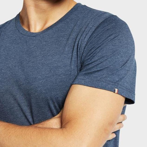 Man wearing Academy Brand Basic Crew cotton t-shirt in navy marle colour.  Close up of sleeve with Academy Brand logo tab on hem.