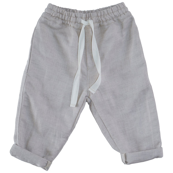 Somebody's Story brand kids pants in sand coloured fabric.   Elasticised waist with white contrast tie.  Rolled hem.