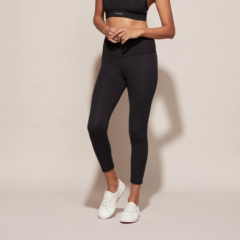 Model wears DK Active Highrider 7/8 Tights in black. Worn with black crop and white casual sneakers.