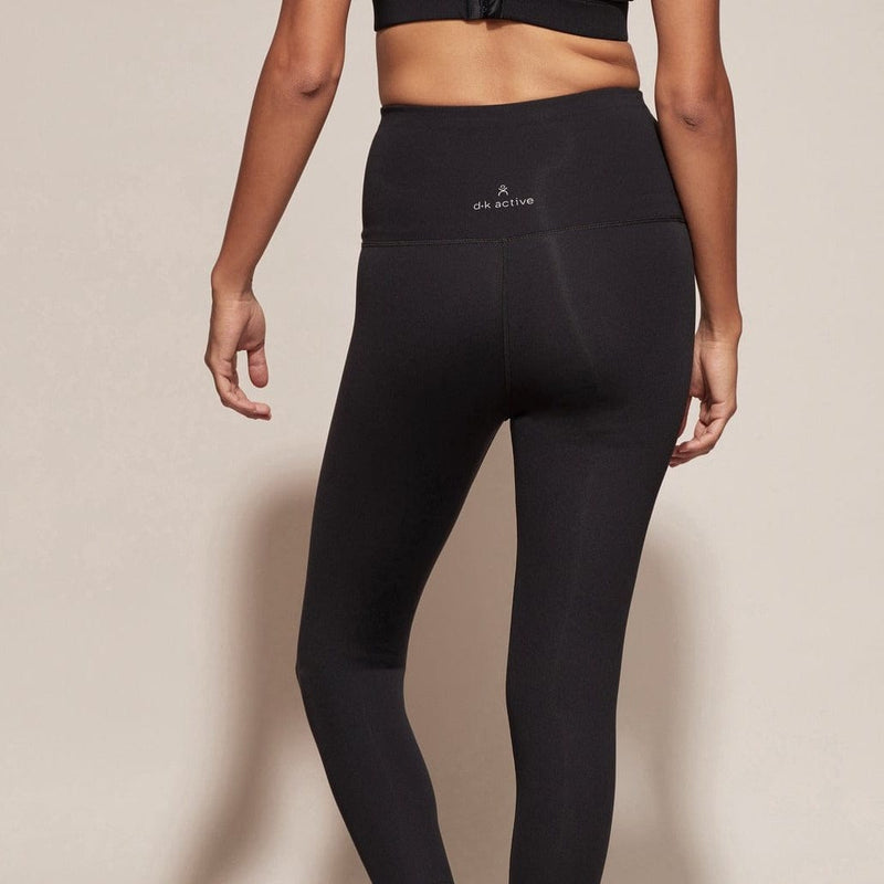 Model wears DK Active Highrider 7/8 Tights in black. Worn with black crop. Back view showing DK Active logo in white.