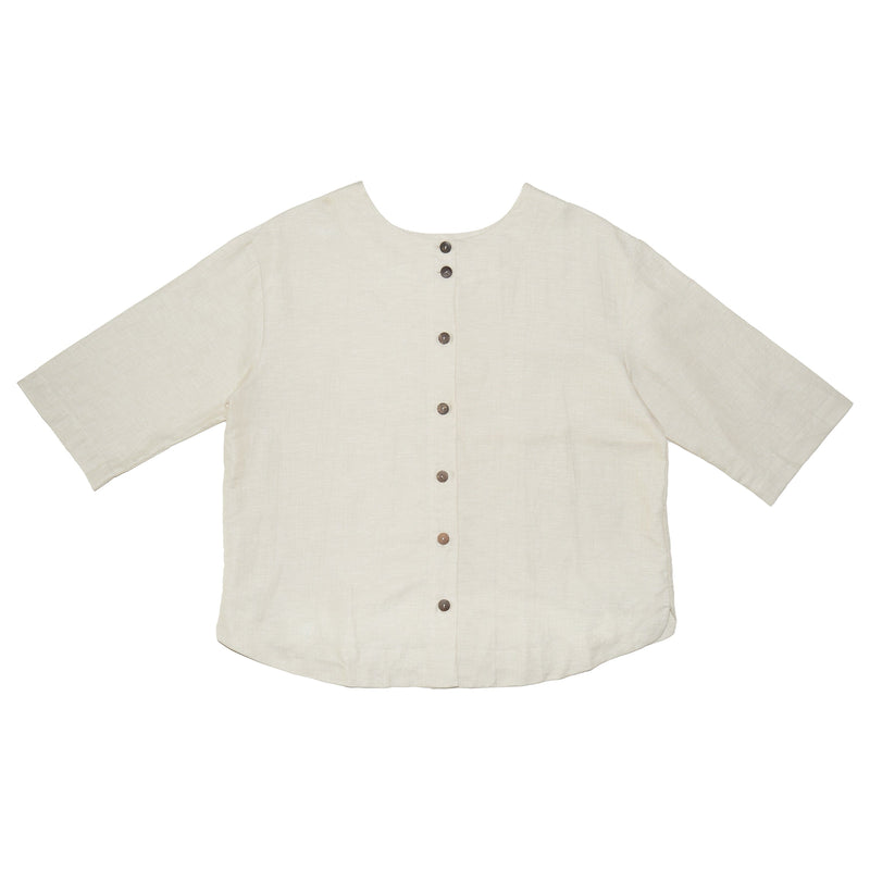 Somebody's Story brand Leonie Top in natural coloured linen. Round, high neck with 3/4 length sleeves and curved hem. Reversed side with button back detail with coconut wood buttons