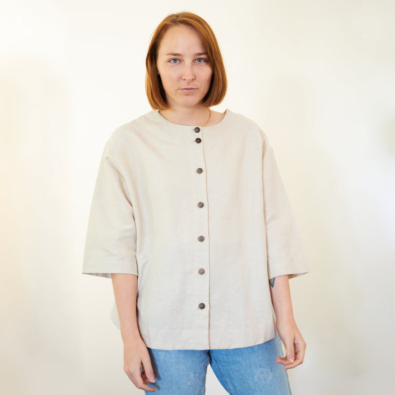 Model wearing Somebody's Story brand Leonie Top in natural coloured linen. Round, high neck with 3/4 length sleeves and curved hem, worn on reversed side with coconut buttons feature. Worn with light blue denim jeans. Front view.