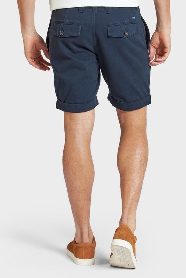 Model wears Academy Brand Santiago Shorts in navy blue colour.  Rolled hem above the knee. Worn with mustard coloured casual shoes.Back view.