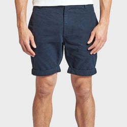 Model wears Academy Brand Santiago Shorts in navy blue colour.  Rolled hem above the knee. Front view.