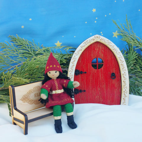 Kindness elf sitting on wooden Elf bench