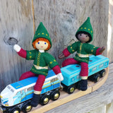 Red haired Kindness elf and black kindness elf dolls sitting on a toy train.