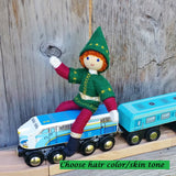 Red haired Kindness elf sitting on a toy train.