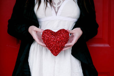 woman in a white dress holding a red heart