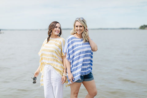 Two young women wearing striped relaxed fit tops and summer bottoms