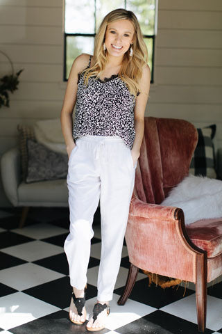 Blonde woman wearing black and white leopard print top with white pants and black sandals